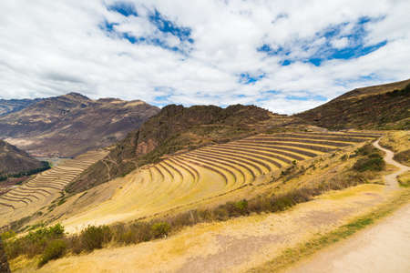 expansive: Expansive view of the glowing majestic concentric terraces of Pisac, Incas site in Sacred Valley, major travel destination in Cusco region, Peru. Dramatic sky. Stock Photo