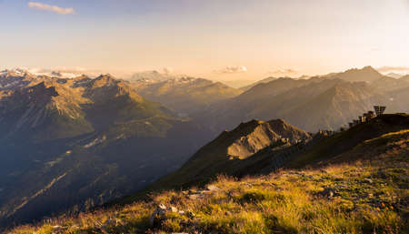 extreme terrain: Last soft sunlight over rocky mountain peaks, ridges and valleys of the Alps at sunset. Extreme terrain landscape at high altitude in Valle dAosta, scenic travel destination in Italy. Stock Photo