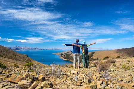 Coppia di turisti con le braccia tese guardando vista sull'Isola del Sole, lago Titicaca, in Bolivia. Concetti di Wanderlust e persone che viaggiano in tutto il mondo. vista espansiva.