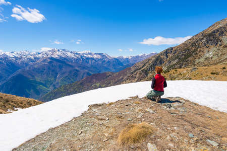 expansive: Hiker kneeling and resting on the scenic mountain summit. Expansive view on the snowcapped alpine arc in the background. Rear view, italian Alps in spring.