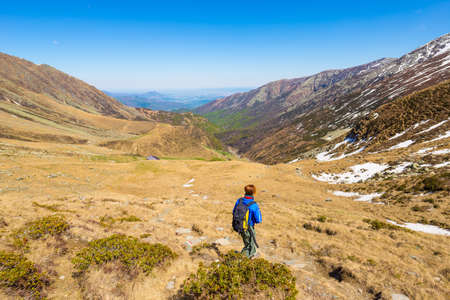 conquering adversity: One backpacker hiking uphill on footpath in the italian Alps. Summer adventures and exploration on the Alps. Wide panoramic view from above.