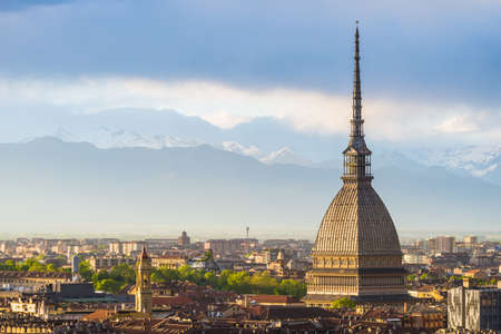 Cityscape of Torino (Turin, Italy) at sunset with details of the Mole Antonelliana towering on the city. Wind storm clouds over the Alps in the background. Фото со стока