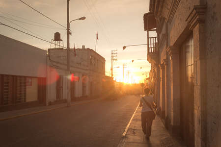 the one person: One person walking alone in a street of Arequipa, Peru, at sunset. Rear view in backlight. Warm toned, lens flare. Stock Photo