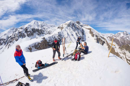 four peaks wilderness: Sestriere, Italy - April 14, 2016: Group of four alpinists chatting in scenic high altitude background on the mountain peak at 3000 m. Italian Alps in a sunny day of springtime. Concept of success and conquering the top.