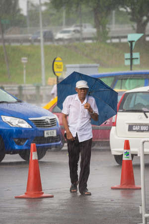 sheltering: Kuching, Malaysia - August 10, 2014: Senior man sheltering under umbrella while raining in the streets of Kuching, West Sarawak, Borneo, Malaysia.