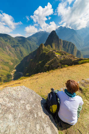contemplation: One person sitting in contemplation of Machu Picchu from the terrace above on daytime. The Incas city is the most visited travel destination in Peru. Stock Photo