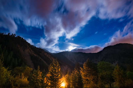 soul searching: The starry sky with blurred motion clouds and bright moonlight, captured from larch tree woodland, glowing by burning fire. Expansive night landscape in the European Alps. Concept of adventure into the wild.