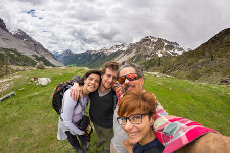 four peaks wilderness: Four young people taking selfie on the Alps with snowcapped mountain range and dramatic sky in background. Scenic fisheye distortion. Concept of traveling people and nature beauty exploration. Stock Photo