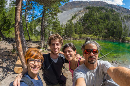 four peaks wilderness: Four young people taking selfies in idyllic landscape with green lake, conifer woodland and mountains in the background. Scenic fisheye distortion. Concept of traveling people and nature beauty exploration.