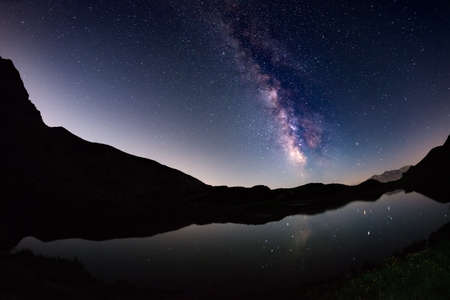 soul searching: The outstanding beauty of the Milky Way arc and the starry sky reflected on lake at high altitude on the Italian Alps, Torino Province. Fisheye scenic distortion and 180 degree view.