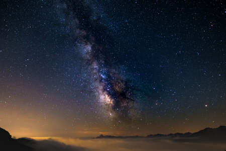 The colorful glowing core of the Milky Way and the starry sky captured at high altitude in summertime on the Italian Alps, Torino Province. Mars and Saturn glowing mid frame.