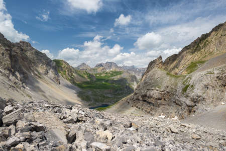 High altitude blue lake in idyllic uncontaminated environment once covered by glaciers. Summer adventures and exploration on the Italian French Alps. Expansive view from above, dramatic sky.