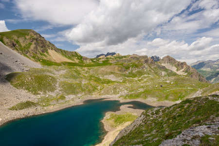 morphology: High altitude blue lake in idyllic uncontaminated environment once covered by glaciers. Summer adventures and exploration on the Italian French Alps. Expansive view from above, dramatic sky.