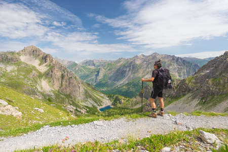expansive: Backpacker hiking on footpath and looking at expansive view from the top. Summer adventures and exploration on the Italian French Alps. Stock Photo