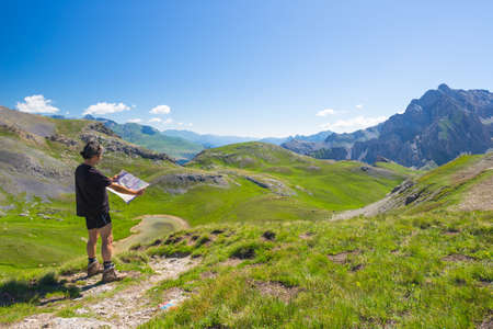 Hiker reading trekking map while resting at panoramic mountain spot. Outdoors activities, summer adventures and exploration on the Italian French Alps. Expansive view from the top.