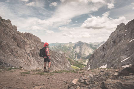 expansive: Backpacker hiking on footpath and looking at expansive view from the top. Summer adventures and exploration on the Italian French Alps. Toned retro vintage styled image.