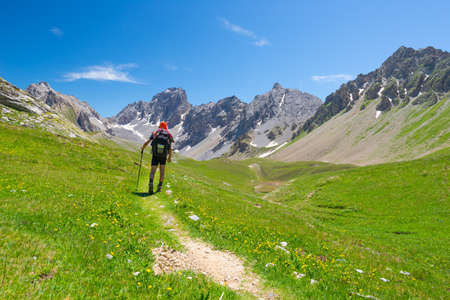 Backpacker hiking on footpath and looking at expansive view from the top. Summer adventures and exploration on the Italian French Alps. Stock Photo