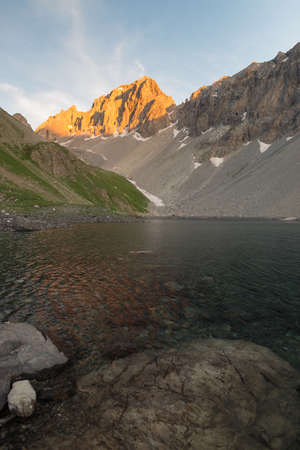 High altitude alpine lake in idyllic land once covered by glaciers. Majestic rocky mountain peak glowing at sunset. Wide angle vertical shot taken on the Italian Alps at 2300 m asl.