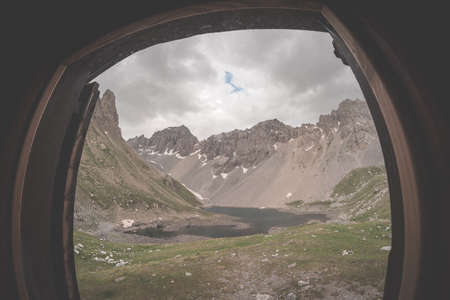 expansive: Looking through window at expansive panorama of alpine valley with lake. Summer adventures and exploration on the Alps. Dramatic sky, toned image.