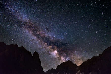 soul searching: The colorful glowing core of the Milky Way and the starry sky captured at high altitude in summertime on the Alps. Scenic snowcapped mountain silhouette.