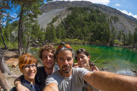 four peaks wilderness: Four young people taking selfie in idyllic landscape with green lake, conifer woodland and mountains in background. Scenic fisheye distortion. Concept of traveling people and nature beauty exploration.
