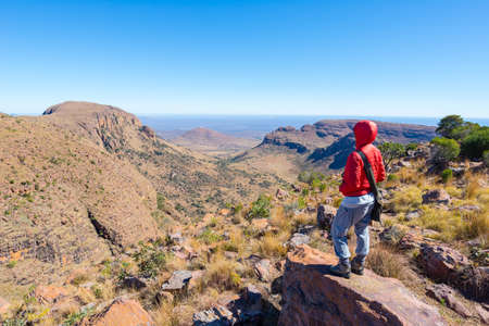Tourist standing on rock and looking at the panoramic view in Marakele National Park, one of the travel destination in South Africa. Concept of adventure and traveling people. Stock Photo