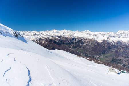 bardonecchia: Wide angle view of a ski resort in the distance with elegant mountain peaks arising from the alpine arc in winter season. Torino Province on Italy France border.