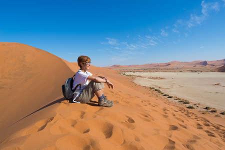 Relaxed toeristische zittend op zandduinen en kijken naar het prachtige uitzicht in Sossusvlei, Namib woestijn, de beste reisbestemming in Namibië, Afrika. Concept van avontuur en reizen mensen.