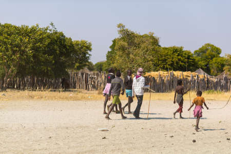 Caprivi, Namibia - August 20, 2016: Poor teenagers walking on the roadside in the rural Caprivi Strip, the most populated region in Namibia, Africa.