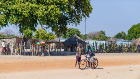 township: Caprivi, Namibia - August 20, 2016: Poor teenagers walking on the roadside in the rural Caprivi Strip, the most populated region in Namibia, Africa.