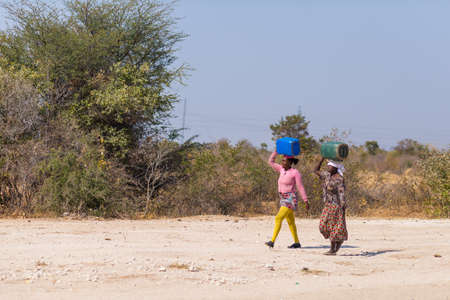 Caprivi, Namibia - August 20, 2016: Poor women walking on the roadside in the rural Caprivi Strip, the most populated region in Namibia, Africa.