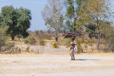 Caprivi, Namibia - August 20, 2016: Poor woman walking on the roadside in the rural Caprivi Strip, the most populated region in Namibia, Africa.