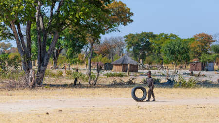 Caprivi, Namibia - August 20, 2016: Poor teenager playing on the roadside in the rural Caprivi Strip, the most populated region in Namibia, Africa.