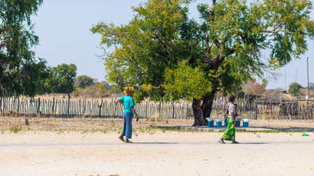 primitivism: Caprivi, Namibia - August 20, 2016: Poor women walking on the roadside in the rural Caprivi Strip, the most populated region in Namibia, Africa.