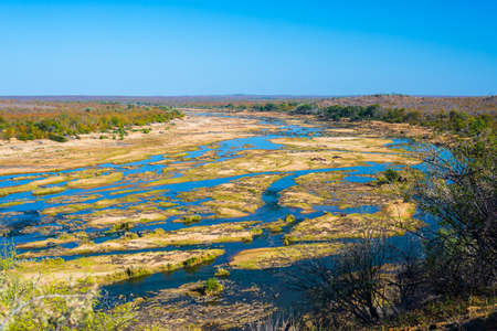 alluvial: Olifants river, scenic and colorful landscape with wildlife in the Kruger National Park, famous travel destination in South Africa. Clear blue sky.