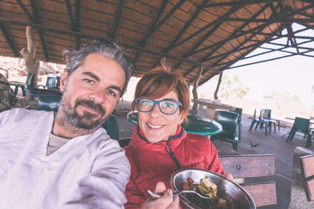 beard woman: Couple taking selfie while having lunch in tourist resort, toned image. Wilderness safari and adventure in Africa. Man with beard, woman with eyeglasses.