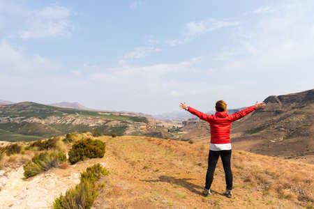 Toerist die zich met uitgestrekte armen en kijken naar het panoramische uitzicht op de majestueuze Golden Gate Highlands National Park, reizen bestemming in Zuid-Afrika. Concept van avontuur en reizen mensen. Stockfoto