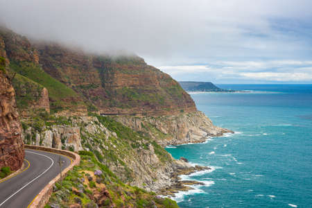 table mountain national park: Chapmans Peak Drive, Cape Town, South Africa. Rough coastline in winter season, cloudy and dramatic sky, waving Atlantic Ocean.