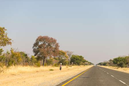 Arme vrouw lopen op de weg in de landelijke Caprivi Strip, de meest bevolkte regio in Namibië, Afrika. Stockfoto
