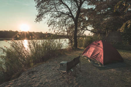 outdoor activities: Camping with tent, chairs and camping gear. Sunrise over Okavango River, Namibia Botswana border. Adventure traveling and outdoor activities in Africa. Toned image, vintage style.