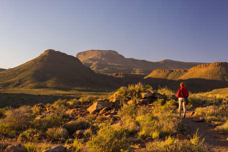 Tourist walking on marked trail in the Karoo National Park, South Africa. Scenic table mountains, canyons and cliffs at sunset. Adventure and exploration in Africa.