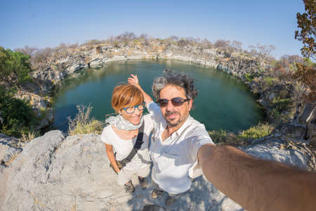 Couple with outstretched arms taking selfie at Otjikoto Lake, one of the only two permanent natural lake in Namibia, Africa. Concept of adventure and traveling people. Fish eye view.