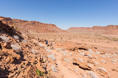 engravings: Twyfelfontein, Namibia - August 27, 2016: Group of tourists walking in the desert at Twyfelfontein, world heritage rock engravings site in Damaraland, Namibia. Concept of adventure and exploration in Africa.