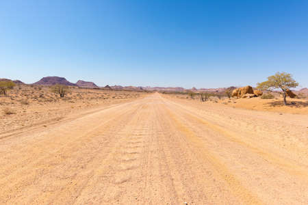 Gravel 4x4 road crossing the colorful desert at Twyfelfontein, in the majestic Damaraland Brandberg, scenic travel destination in Namibia, Africa. Stock Photo
