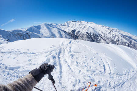 Subjective personal view of alpin skier on snowy slope ready to start skiing. Expansive fisheye panorama of the italian Alps with clear blue sky. Concept of wanderlust and adventures on the mountain.