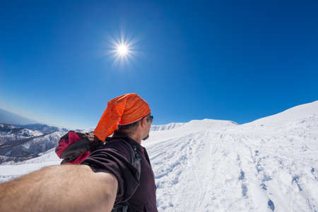 Adult alpin skier with beard, sunglasses and hat, taking selfie on snowy slope in the beautiful italian Alps with clear blue sky. Concept of wanderlust and adventures on the mountain. Wide angle fisheye lens.
