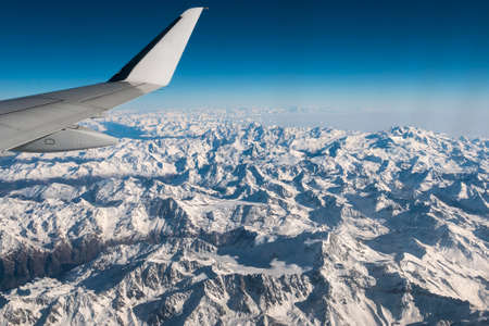 expansive: Aerial view of the Italian Swiss Alps in winter, with generic aeroplane wing. Snowcapped mountain range and glaciers. Expansive view, clear blue sky.   Stock Photo