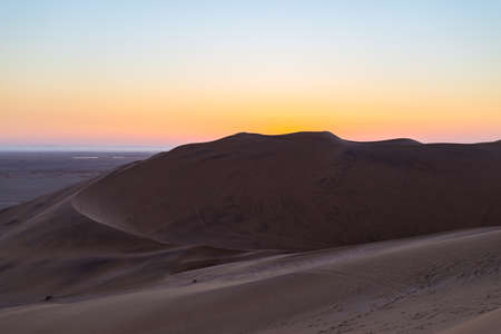 ridge of wave: Colorful sunset over the Namib desert, Namibia, Africa. Scenic sand dunes in backlight in the Namib Naukluft National Park, Swakopmund.