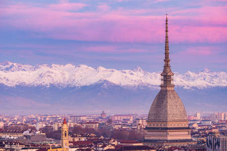 Torino (Turijn, Italië): stadsgezicht bij zonsopgang met details van de Mole Antonelliana torenhoge over de stad. Toneel kleurrijk licht op de sneeuw bedekte Alpen op de achtergrond.