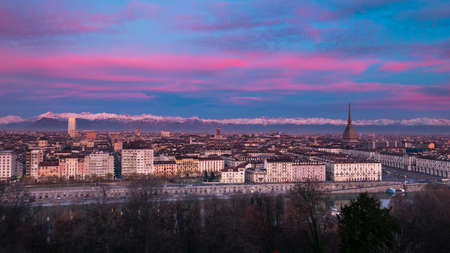Torino (Turin, Italy): expansive cityscape at dusk with scenic colorful light on the snowcapped Alps in the background.